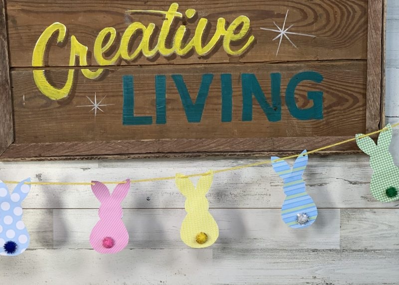 Creative Living Sign with bunny garland on it