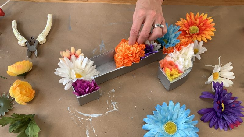 Arranging flowers into the letter casing and gluing
