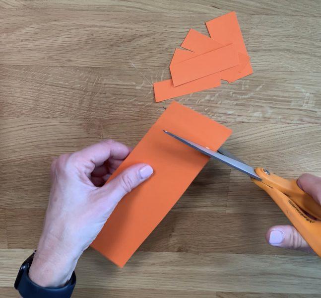 Cutting strips of paper to create paper leprechaun beard