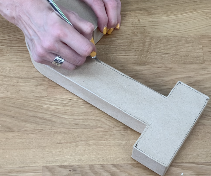 Using a precision blade to cut the front face off the 3D letter