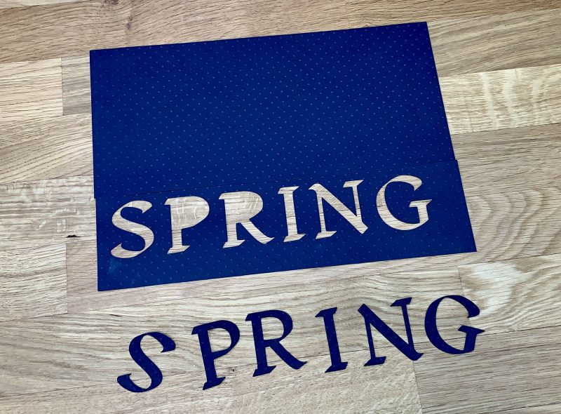 SPRING letters cut out of black card stock