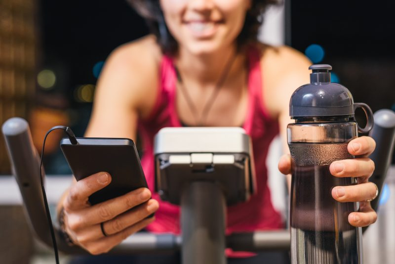 Woman working out with her app and water on a cycle