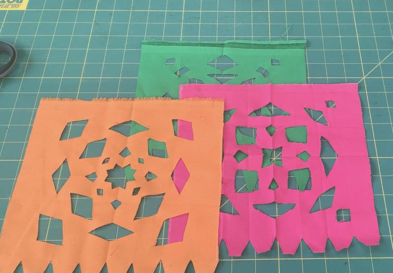 Multiple fabric squares cut into papel picado